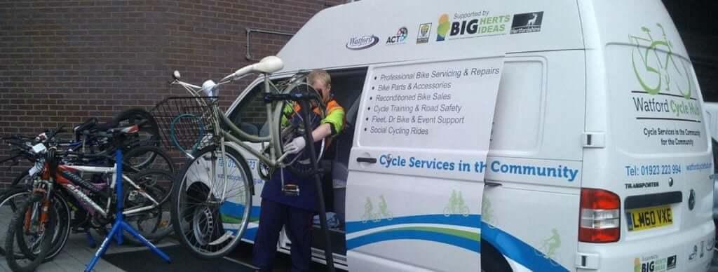 Mechanic working on a bicycle with the Watford Cycle Hub mobile workshop van